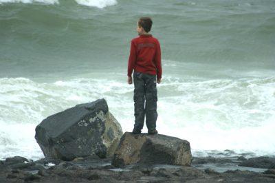 Jongen kijkt uit over zee